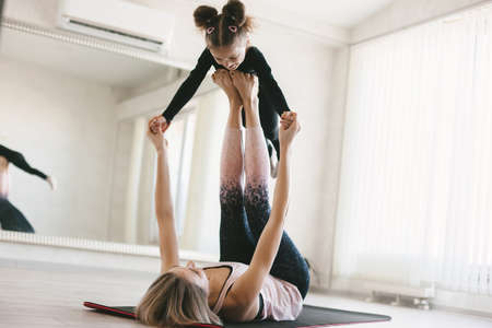 Beautiful sporty woman and little child girl doing together stretching exercise on yoga mat in front of mirror in fitness class Stok Fotoğraf