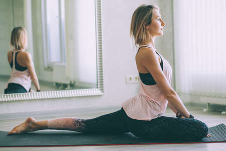Young woman doing stretching exercise by mirror on floor mat in bright yoga class room. Standard-Bild - 157336185