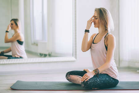 Young woman sitting in yoga pose and meditating by mirror on floor mat in bright class room.