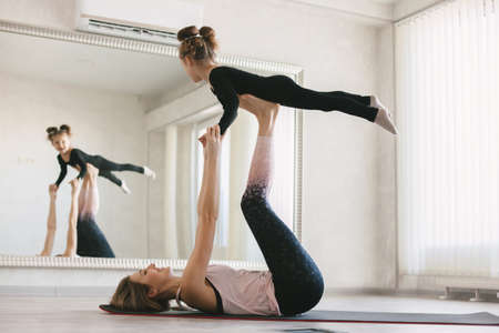 Beautiful sporty woman and little child girl doing together stretching exercise on yoga mat in front of mirror in fitness class Standard-Bild