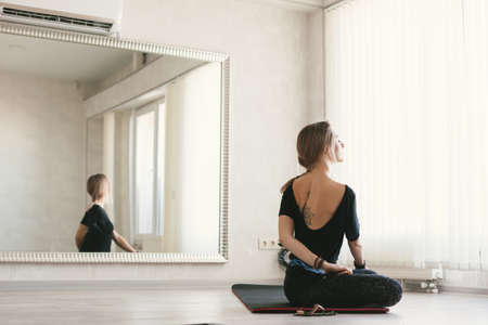 Young woman doing stretching exercise by mirror on floor mat in bright yoga class room wirh air conditioner.
