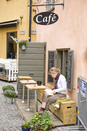 Young woman in the street cafe in the old city Camla Stan in Stockholm