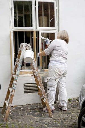 The house painter paints a window. Taken in Copenhagen, Denmark