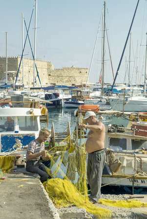 Fishermen examine fishing nets  Taken o Crete, Greece