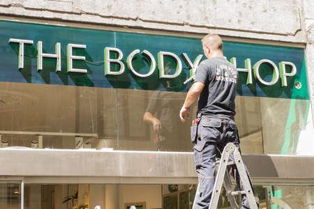 advertizing: Copenhagen Denmark -August 2012  The worker installs outdoor advertizing of cosmetic shop