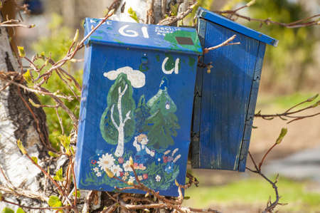 Two wooden mailboxes decorated by drawings  Taken in Norway