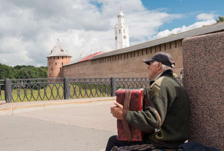 Novrorod Kremlin, Russia - September 16, 2013. The elderly man plays on an accordion in front of the Novgorod Kremlin.