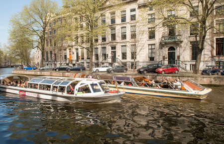 tour boats: Amsterdam, The Netherlands - April 05, 2014; An Amsterdam Canal Cruise is most popular tourist attraction . A diverse fleet of around 200 tour boats carry more than 3 million passengers a year.