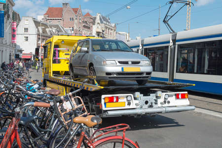 Amsterdam, The Netherlands - April 05, 2014; Tow Truck urban towing away a wrongly parked car in Amsterdam.