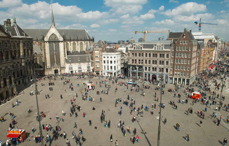 Amsterdam, The Netherlands - April 05, 2014; The Dam square is the very centre and heart of Amsterdam and has seen many historical dramas. The big attractions in Dam Square, Royal Palace.  Although no longer home to the Dutch Royal family, this grand 17th Editorial