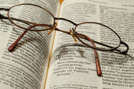 Round glasses lie on the bible in the Swedish language Stock Photo
