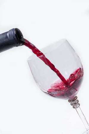 Stream of red wine on white background. Stock Photo