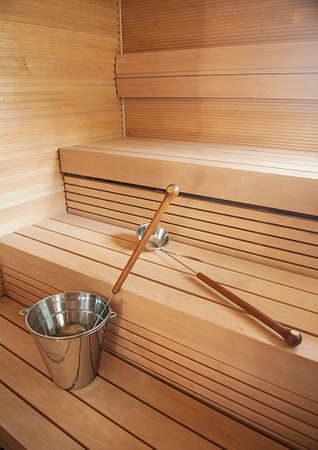 Bucket and scoop in wooden finnish sauna background. Stock Photo