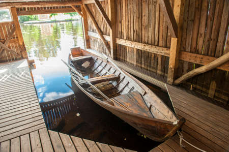 Wooden boat in the pier under canopy. Taken in Finland.