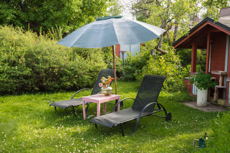 Traditional private garden with wooden chair and umbrella the summer day. Taken in Finland, 2019 Stock Photo