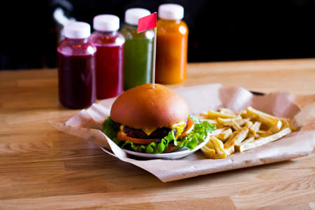 burger and french fries on the wooden table Фото со стока