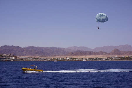 beach activity: parasailing, high-speed boat pulls a girl on a parachute. Sea and mountains on the background