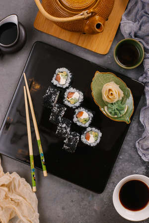 Sushi Set nigiri and sushi rolls in dark ceramic plate with soy sauce, iron teapot and chopsticks over black stone texture background. 写真素材