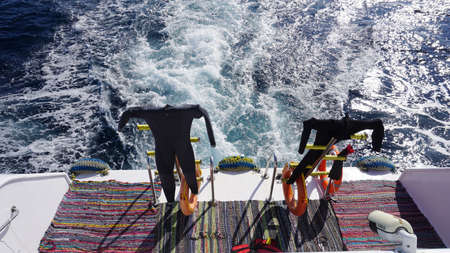 Hanging wetsuits at scuba diving boat waiting for Imagens
