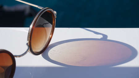 Fashion sunglasses on sea beach under clear blue sky. Summer holiday relax background with copy space.