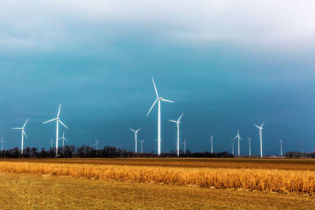 Windmills for electric power production on the background of a stormy sky