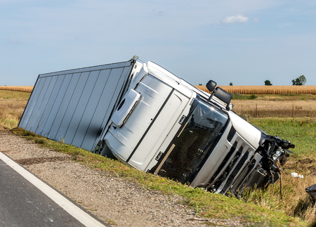 The truck lies in a side ditch after the road accident.