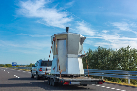 Car with unusual kiosk in the form of Espresso Coffee Maker Moka Pota on a trailer on the highway
