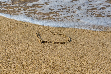 Heart drawn on wet sand beach. Part of the heart is washed away by a wave. Symbol of the beginning or the end of romantic love. Summer vacation concept. Romantic background with space for text