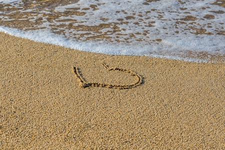 Herz gezeichnet auf nassem Sandstrand. Ein Teil des Herzens wird von einer Welle weggespült. Symbol für den Anfang oder das Ende der romantischen Liebe. Sommerferienkonzept. Romantischer Hintergrund mit Platz für Text