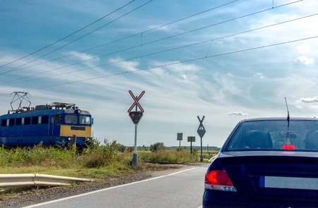 The electric train approaching railroad crossing. Car standing in front of the railway crossing with traffic light and road sign without a barrier Banco de Imagens