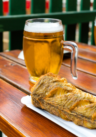 Fried fish on disposable paper plate and chilled glass of draft beer on wooden table in outdoor cafe. Selective focus Imagens
