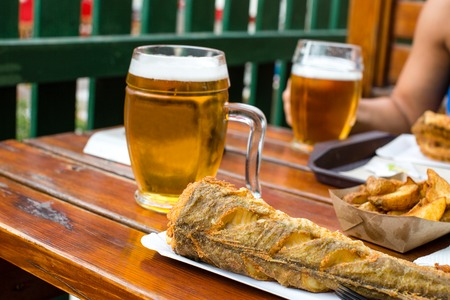 Delicious fried fish and potatoes on disposable paper plate and chilled glass of draft beer on wooden table in outdoor cafe. Selective focus