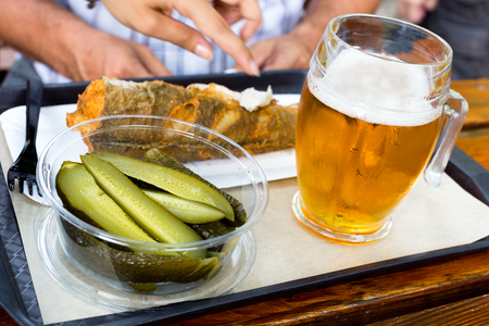 Delicious fried fish, pickled cucumbers and chilled glass of draft beer on a tray on wooden table in outdoor cafe Imagens