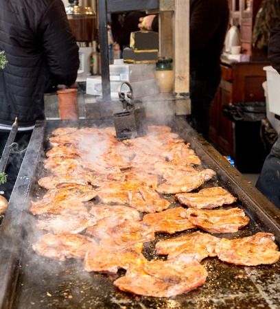Juicy meat steaks grilling on the barbeque under vintage iron grill press at street food festival Imagens