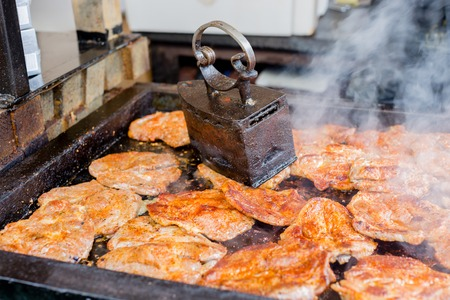 Juicy meat steaks grilling on the barbeque under vintage iron grill press at street food festival Zdjęcie Seryjne