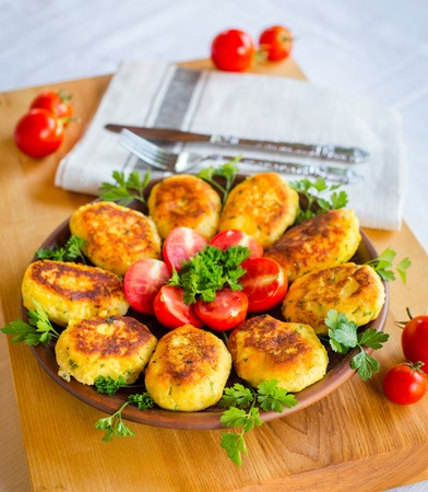 Homemade ruddy cheese and potato cutlets, decorated with fresh tomatoes and parsley, in ceramic plate on wooden board