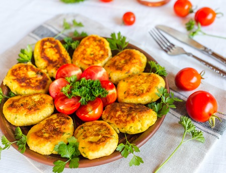 Homemade ruddy cheese and potato cutlets, decorated with fresh tomatoes and parsley, in ceramic plate on napkin Imagens