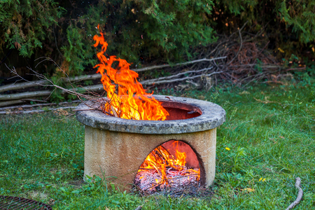 Dry branches burn in isolated campfire pit in the garden. High bright flames flickering on open garden fire pit.