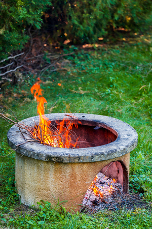 Dry branches burn in isolated campfire pit in the garden. High bright flames flickering on open garden fire pit. Vertical photo Imagens
