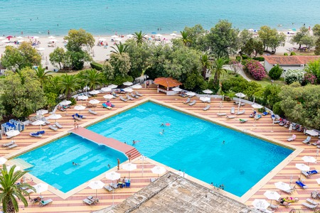 Beautiful view of outdoor swimming pool area with clear blue water, sunbeds and umbrella around. View of the sea shore with figures of tourists. Summer vacation and tourism concept