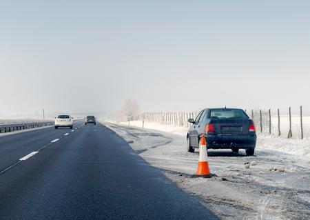 Faulty car and traffic cone on emergency stopping lane on the roadside. Problem with vehicle on winter highway. Imagens