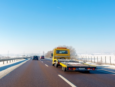 Yellow tow truck with empty platform moves on highway in winter