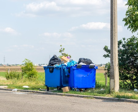 Overflowing blue plastic waste cans with black garbage bags, cardboard boxes and other garbage outside the city near the road. One waste can is broken