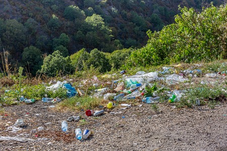 Plastic bottles and other trash along the mountain road in Macedonia. A lot of trash at roadside. Concept of environmental pollution