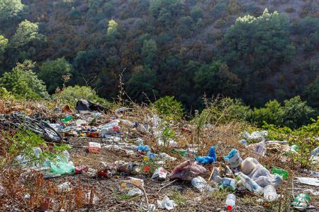 Plastic bottles, bags and other trash along the road. Trash at roadside. Concept of environmental pollution