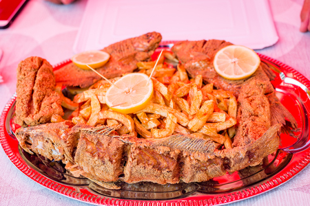 Delicious fried trout fish and catfish pieces, fried potatoes, decorated with lemon slices on disposable paper plate. Fresh fish from Tisza river