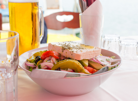 Bowl of Greek salad with feta cheese, green pepper, tomato, olives and red onion. Beer mug and empty glasses on table Imagens