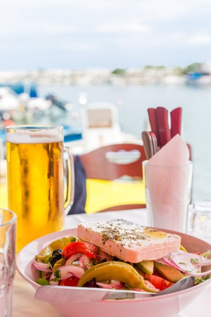 Bowl of fresh Greek salad with feta cheese, green pepper, tomato, cucumber, olives and red onion. Greek salad and beer mug on table against the sea bay background in Greece