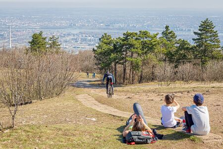 Budapest, Hungary - March 17, 2019: Family resting in nature, two boys sitting on the hill, woman lies on the ground and looks smartphone, man down the hill on a bicycle. Good weather, beautiful view of Budapest city. Relationship between humans and natur