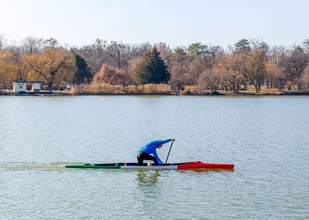 Man rowing in canoe with paddle , standing on one knee. Athlete trains on the lake